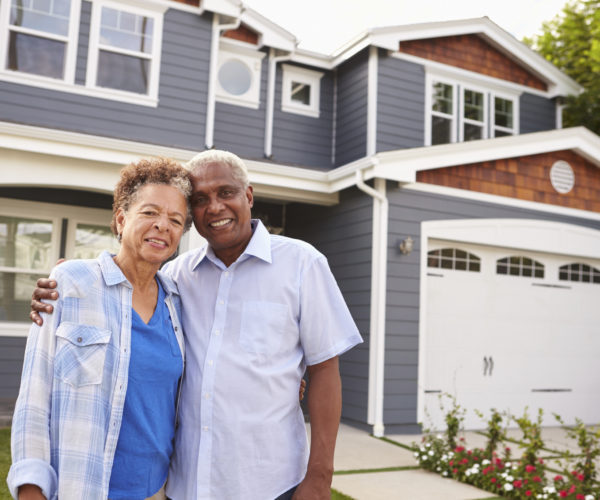 Senior-african-american-couple-standing-outside-a-large-suburban-house