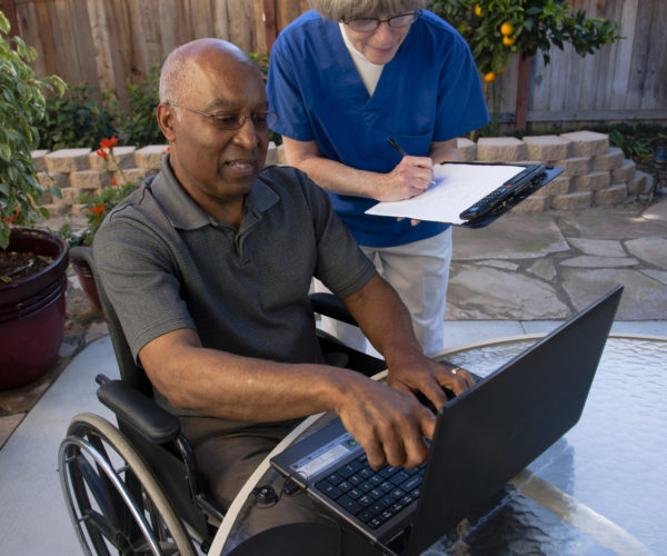 Healthcare-worker-helping-disabled-senior-with-computer
