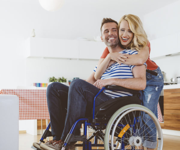 Happy-disabled-man-sitting-in-a-wheelchair-in-the-domestic-kitchen-his-wife-embracing-him